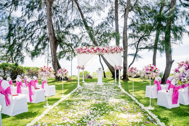 Beach wedding venue arch, altar decorated with pink, white, red roses and flowers