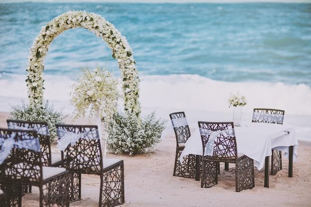 아치에 꽃 장식으로 해변 결혼식 장소 설정
