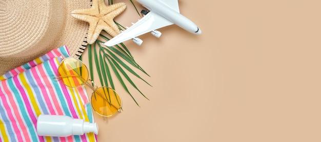 ビーチの籐のわら、明るい縞模様のドレス、spfクリーム、サンダル緑の熱帯の葉と砂の上の黄色いサングラス