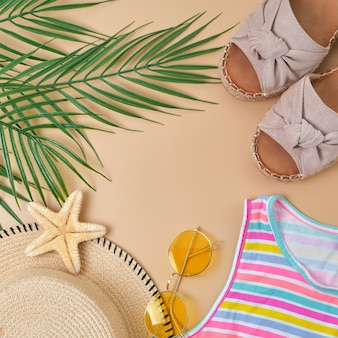ビーチの籐のわら、黄色のサングラス、明るい縞模様のドレス、サンダル、ベージュの砂の上の緑の熱帯の葉