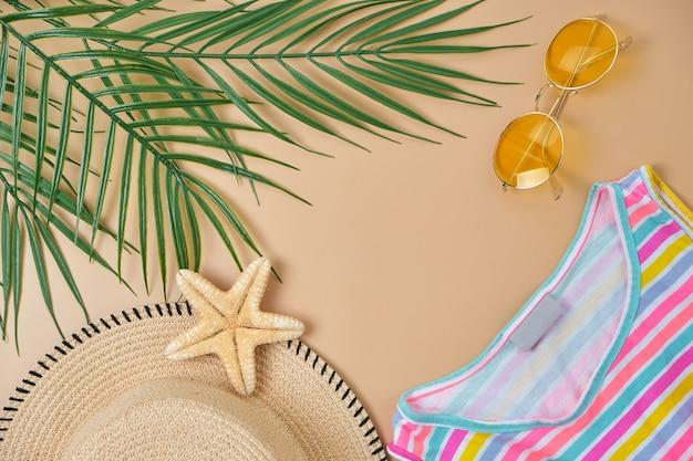 ビーチの籐のわら、黄色のサングラス、明るい縞模様のドレス、サンダル、ベージュの表面に緑の熱帯の葉