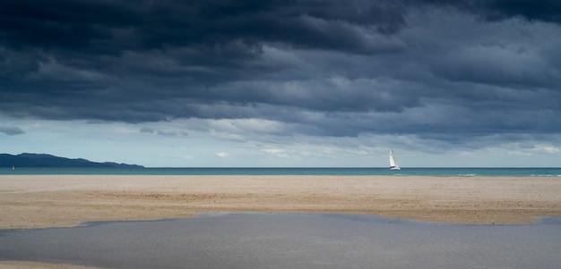 Пляж с парусной лодкой. концепция свободы