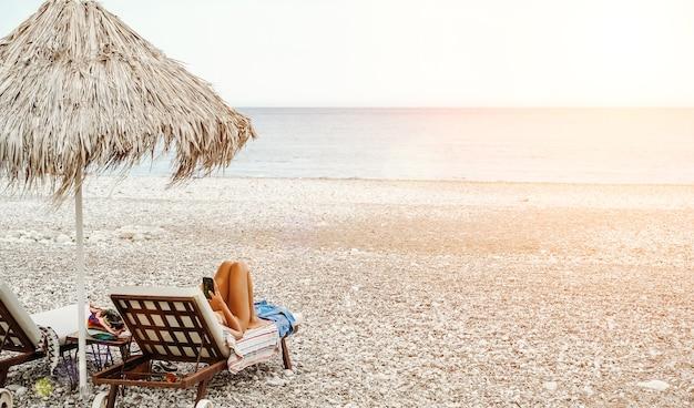 Пляж с женщиной, отдыхающей в шезлонге, отдых и релаксация на море, пляж под высоким солнцем ...