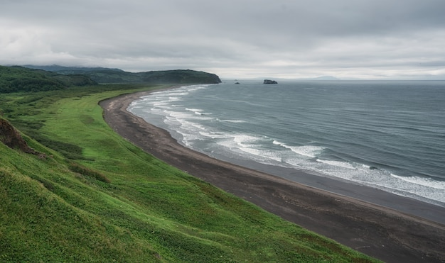 Beach with black sand and waves in pacific ocean shore on kamchatka