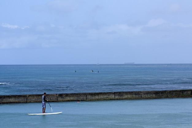 Spiaggia con un mare blu e gente che si diverte alle hawaii, usa