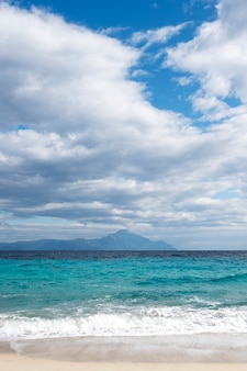 A beach with blue waves of the aegean sea and mountain