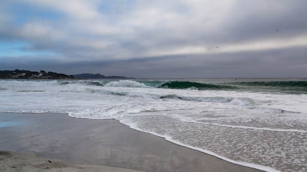 嵐の夕日の海の波とビーチ
