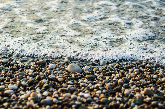 Beach with pebbles and surf at dusk or dawn