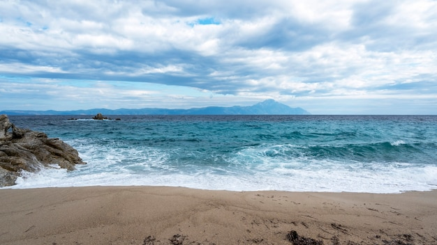 A beach with rocks and blue waves of the aegean sea, land and mountain