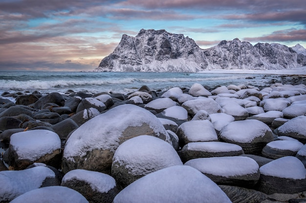 雪に覆われた岩とロフォーテン諸島、ノルウェーの背景の山々とビーチ