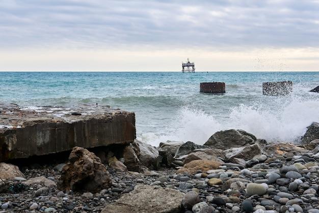 産業構造物の廃墟と海のはるか遠くにある厄介な養殖施設のあるビーチ