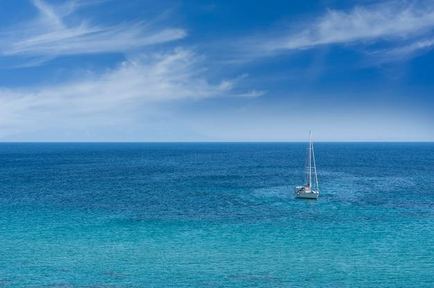 Пляж с парусной лодкой в море, чешме - турция