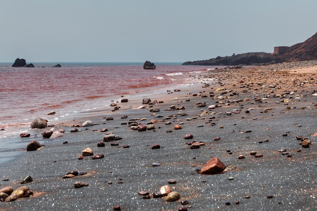 Hormuz, hormozgan,이란에 은색 모래와 붉은 바다 물이있는 해변.