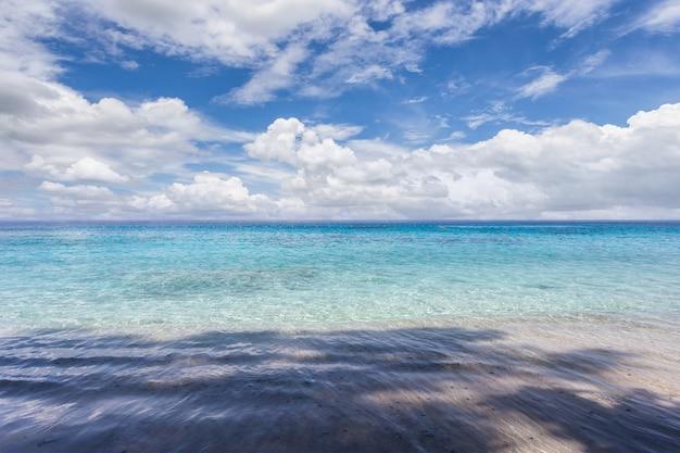 Пляж с бирюзовой водой и облаками на пейзаже голубого неба