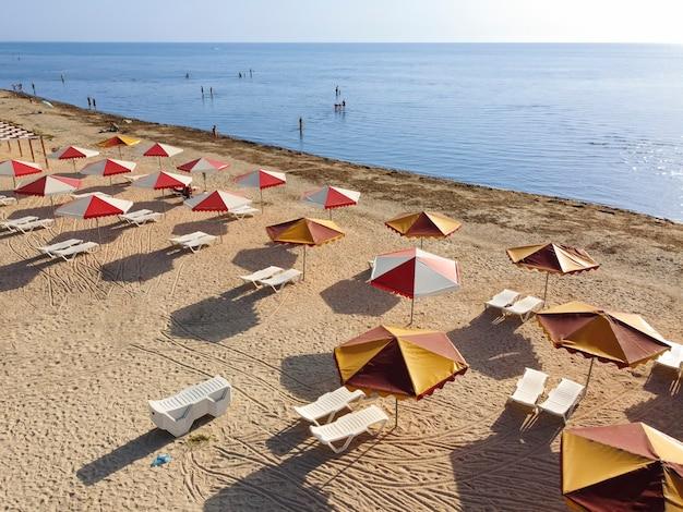 Пляж с зонтиками и грязное море, приносящее на берег множество водорослей.