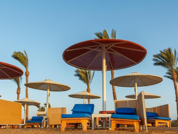 Пляж с зонтиками и шезлонгами на фоне голубого неба.