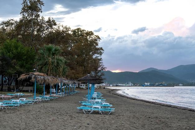 Пляж с зонтиками и шезлонгами на берегу эгейского моря, греция