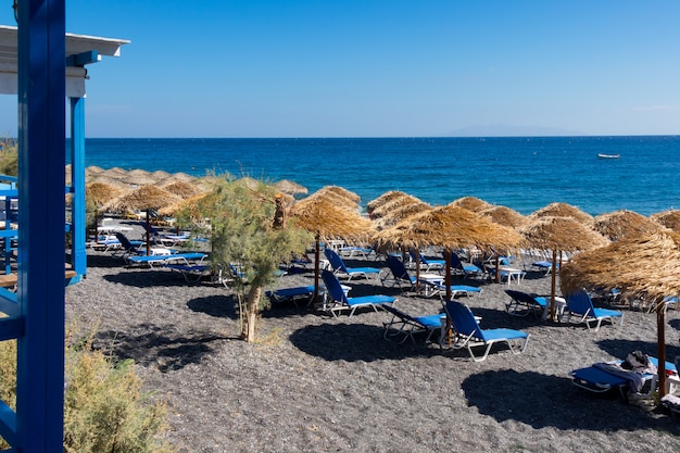 Beach with umbrellas and deck chairs by the sea in santorini
