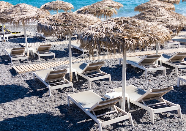 Beach with umbrellas and deck chairs in santorini