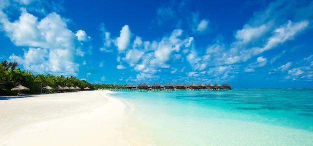 Пляж с белым песком, бирюзовой водой океана и голубым небом с облаками в солнечный день. естественный фон для летних каникул. панорамный вид.