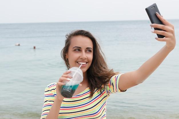 해변 파티에서 즐거운 시간을 보내는 차가운 음료수를 마시는 해변 여성. 아이스 티, 콜라 또는 알코올 음료를 즐기는 비키니 입은 여성 아기가 행복하게 웃고 있습니다. 셀카 사진을 찍는 스마트 폰 장치를 들고