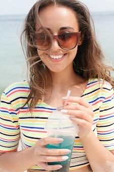 Женщина пляжа, пить холодный напиток, весело на пляжной вечеринке. младенец женского пола в бикини, наслаждаясь холодным чаем, колой или алкогольным напитком, улыбаясь счастливым смехом, глядя в камеру. красивая девушка смешанной расы