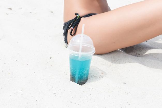 해변 파티에서 즐거운 시간을 보내는 차가운 음료수를 마시는 해변 여성. 아이스 티, 콜라 또는 알코올 음료를 즐기는 비키니 입은 여성 아기가 카메라를 보며 행복하게 웃고 있습니다. 아름다운 혼혈 소녀