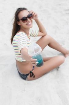 ビーチパーティーで楽しんで冷たい飲み物を飲むビーチの女性