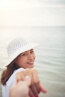 Beach woman holding hand happy