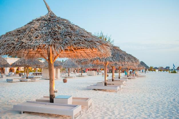 Пляжные деревянные шезлонги и зонтики для отдыха на пляже в греции