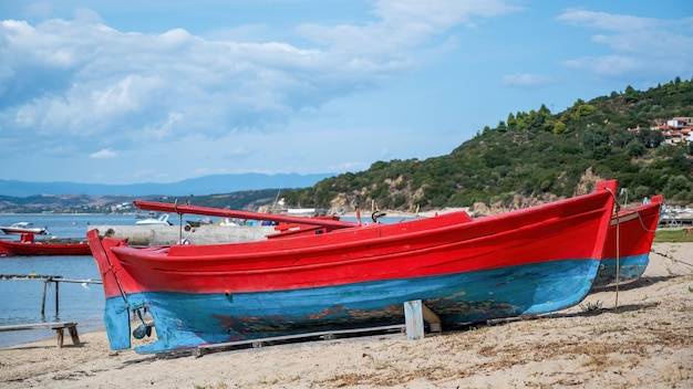 Beached wooden colored boats on aegean sea cost, pier, yachts and hills in ouranoupolis, greece