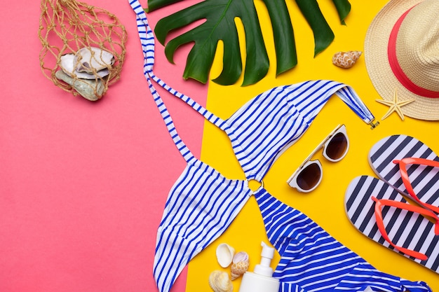 Beachwear and accessories on a pink and yellow