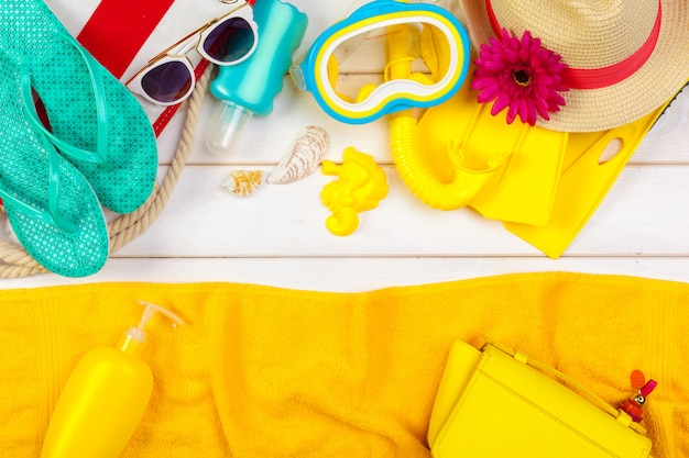Beachwear and accessories on a white wooden background