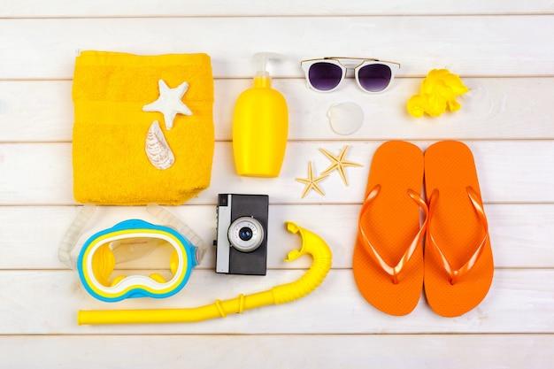 Beachwear and accessories on a white wooden