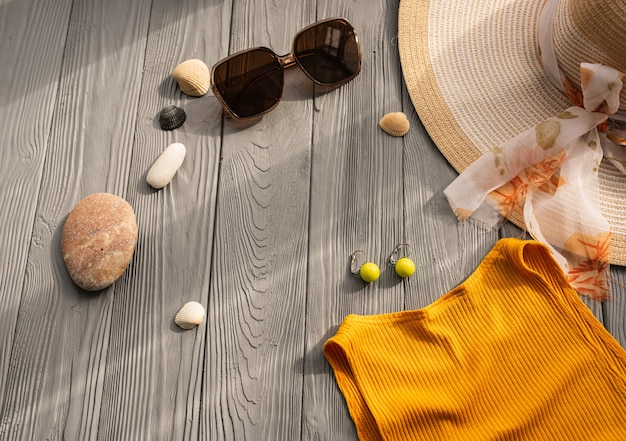 ビーチウェアオレンジ女性トップ衣装帽子バッグ日焼け止めサングラス小石。夏の背景