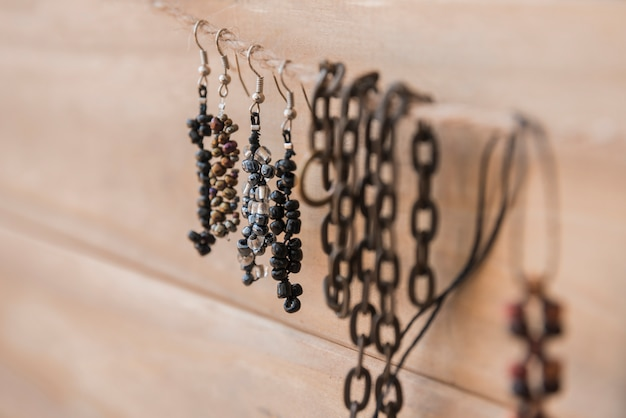 Beads earrings and bracelet hanging on string against wooden wall