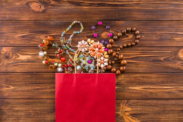 Beads jewelry and red paper bag on wooden background