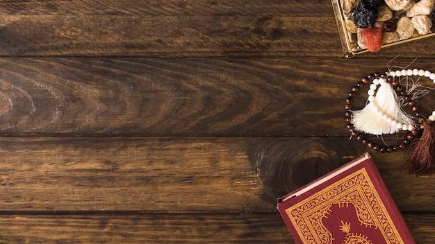 Бусины возле религиозной книги и конфет