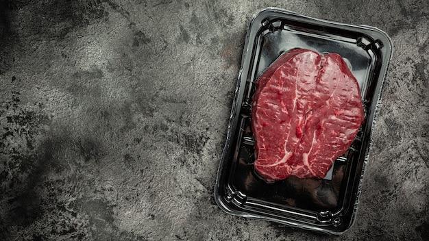 Бифштекс готов к приготовлению в вакуумной упаковке. . мясные продукты в упаковке на черном фоне, мясные полуфабрикаты. вид сверху.
