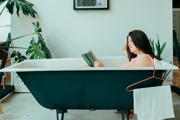 緑の植物とフランス風の部屋で装飾的な内部空ヴィンテージ鋳鉄風呂で横になっているピンクのドレスの若いbeaitoful女の子。