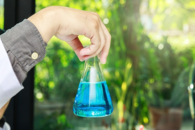 Beaker with blue experiment liquid in scientist hand on laboratory background, science concept.