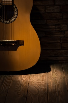 A beam of light illuminates an acoustic guitar standing against a wall on a wooden floor.