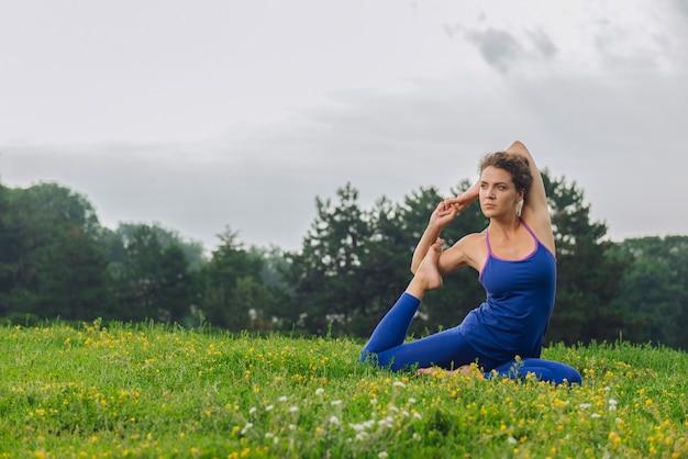Сияющая кудрявая женщина чувствует себя свободной и спокойной, улучшая свою гибкость с помощью растяжки