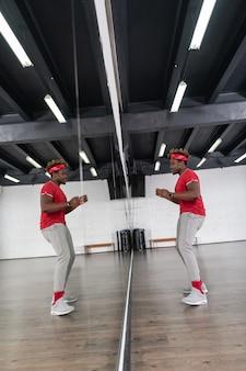 広々とした鏡の前で踊りながら楽しんでいる明るい髪のアクティブな男