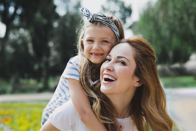 빛나는 딸. 그녀와 함께 시간을 보내는 동안 그녀의 사랑하는 웃는 어머니를 포옹하는 귀여운 빛나는 딸