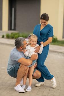 Сияющая дочь. любящие заботливые родители обнимают свою сияющую красивую дочь