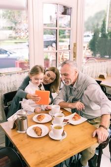 빛나는 조부모. 귀여운 작은 손녀와 함께 아침 크로와상을 먹는 행복 한 전송 조부모