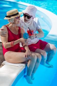 Сияющие зрелые мужчина и женщина пьют летние напитки, сидя у большого открытого бассейна