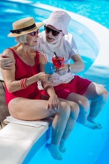 Beaming mature man and woman having summer drinks while sitting near big outside pool