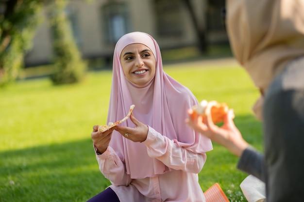 빛나는 학생. 가장 친한 친구가 잔디에 앉아 피자를 먹는 검은 눈을 가진 이슬람교도 학생